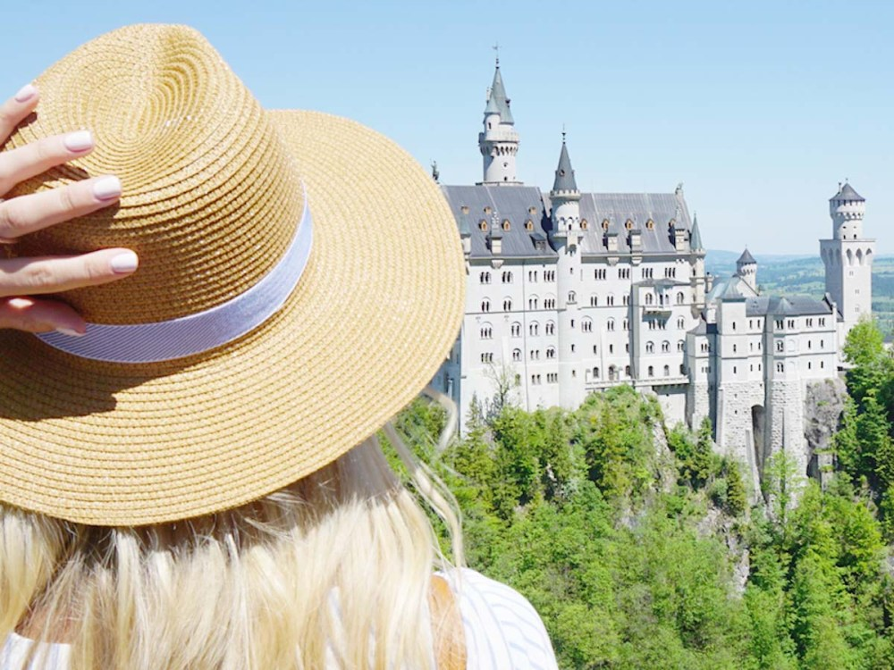 Blonde girl with hat looking at Neuschwanstein Castle from Marienbrucke