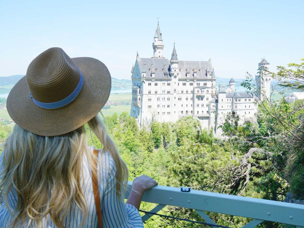 Blonde girl in hat looking at Neuschwanstein Castle from Marienbrucke
