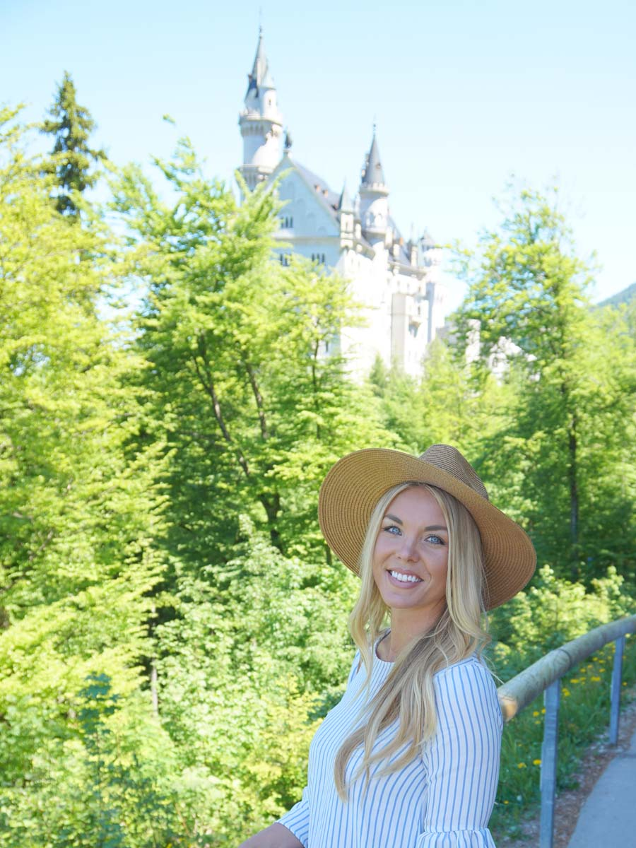 Blond girl smiling on path Tegelbergbahn with castle in background