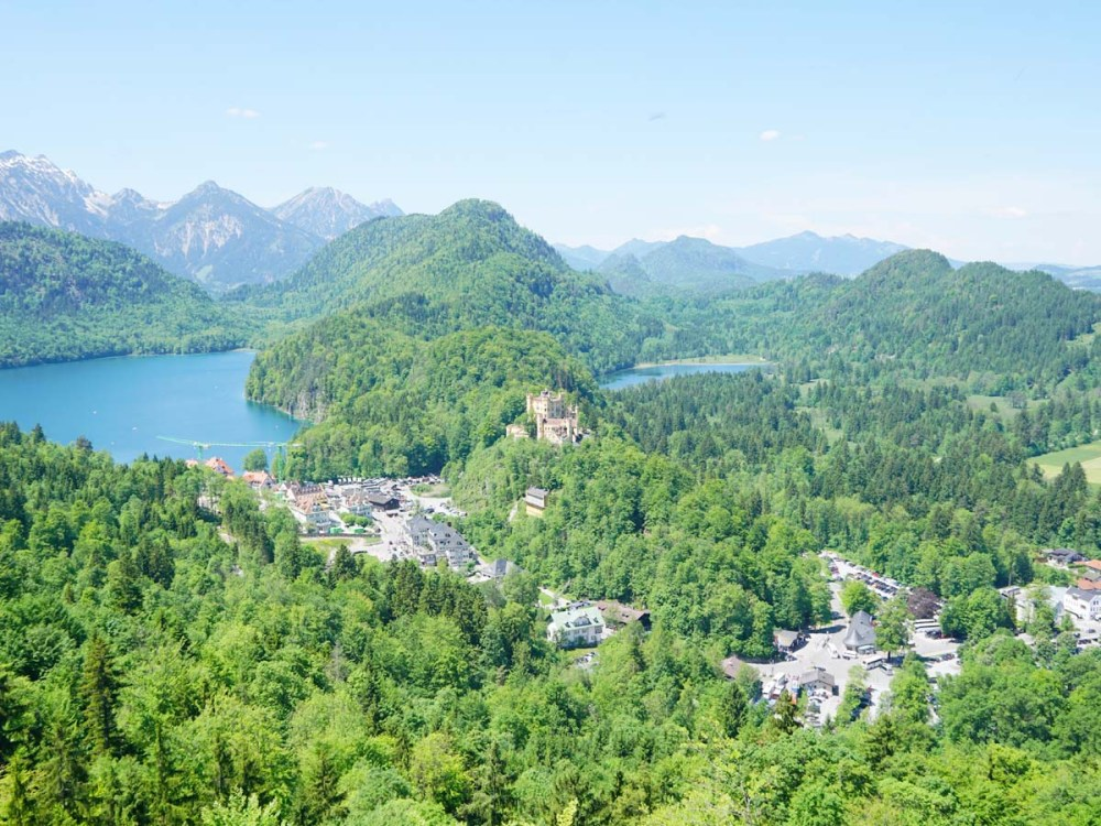 Viewpoint of Hohenschwangau Castle and the surrounding area with the town and lakes below