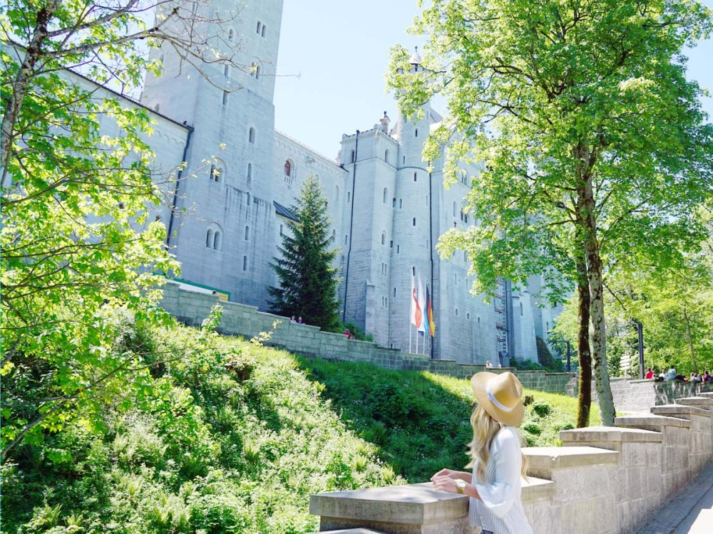 Blonde girl looking at Neuschwanstein Castle from bottom of the hill